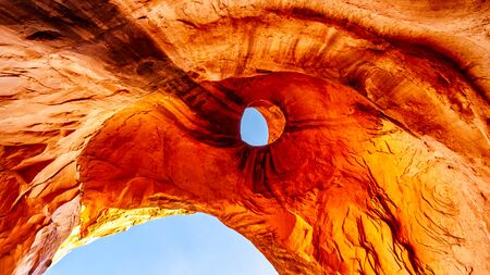 The weather stained ceiling the Big Hogan arch, a large arch in Monument Valley Navajo Tribal Park on the Utah and Arizona border, USA. It is shaped like an Eagles Head with the hole forming the Eye
