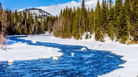 Snow and ice lining the Murtle River in winter time in the Cariboo Mountains of Wells Gray Provincial Park, British Columbia, Canada