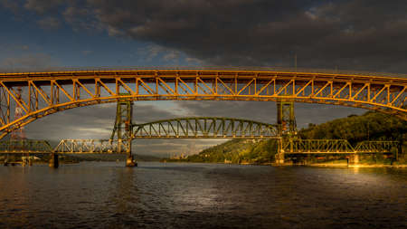 Sunset over the Second Narrows Bridge (Ironworkers Bridge) of the Trans Canada Highway and a Railway Bridge, over Burrard Inlet and Vancouver Harbor