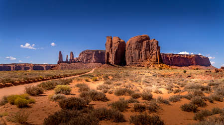 The Three Sisters and Mitchell Mesa, a few of the many massive Red Sandstone Buttes and Mesas in Monument Valley, a Navajo Tribal Park on the border of Utah and Arizona, United States Фото со стока