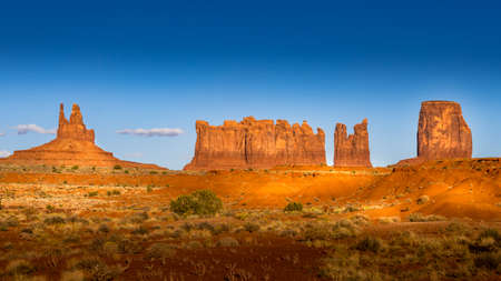 The sandstone formations of Mitten Buttes and Cly Butte in the desert landscape of Monument Valley Navajo Tribal Park in southern Utah, United States
