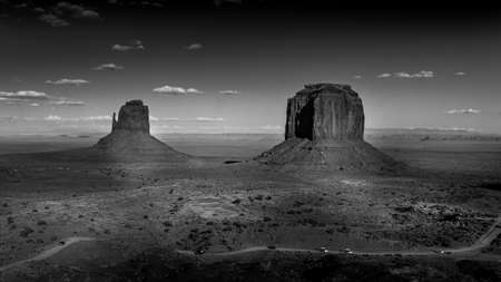 Black and White Photo of the sandstone formations of West Mitten Butte and Merrick Butte in the desert landscape of Monument Valley Navajo Tribal Park in southern Utah, United States Фото со стока