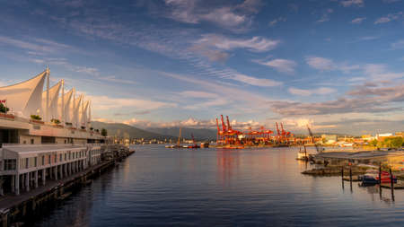 Vancouver, BC/Canada - July 16, 2020: Sunset over the Vancouver Container Port and Harbour between the Canada Place Cruise Terminal and the Waterfront Skytrain and Seabus Terminal