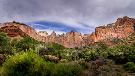 The Red Sandstone Mountains viewed from the Pa'rus Trail which follows along and over the meandering Virgin River in Zion National Park in Utah, USA Archivio Fotografico