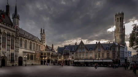 Brugge/Belgium - Sept. 18 2018: Evening at the Historic buildings of the Town Hall and Basilica of the Holy Blood on Burg Square with the Belfry Tower in the background in the city of Bruges, Belgium