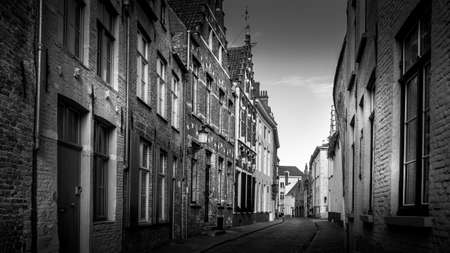 Black and White Photo of a Typical cobblestone street with brick houses in the historic city of Bruges, Belgium