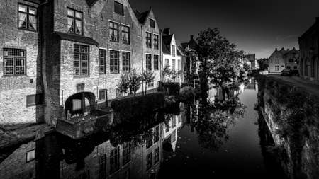 and White Photo of Medieval houses reflecting in the waters of a canal in Bruges, Belgium