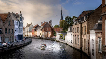 Brugge / Belgium - Sept. 18, 2018: Canal boat ride on the St. Annarei canal in the historic city of Bruges, Belgium with the steel Lanchals sculpture and the tower of the St. Anna Church on the right