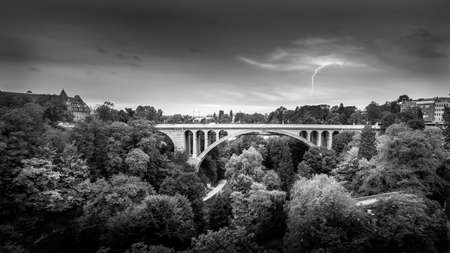 Black and White Photo of the Pont Adolphe (Adolphe Bridge) and Vall de la Ptrusse (Petrusse Park), with  a Lightning Strike in the distance in the city of Luxumbourg Stok Fotoğraf