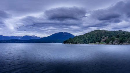 Dark Clouds and a Flock of Birds during a Ferry trip between Horseshoe Bay and Sechelt in British Columbia, Canada