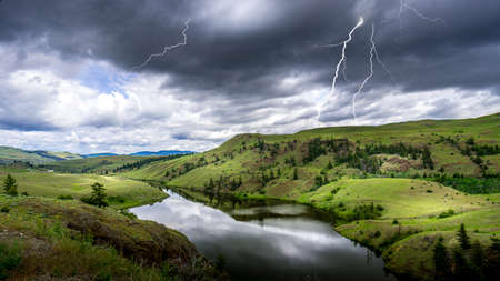 Lightning Strikes from Dark Clouds over Napier Lake in the Grasslands along Highway 5A between Kamloops and Merritt in British Columbia, Canada Stok Fotoğraf