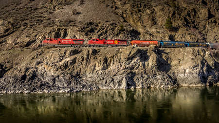 Spences Bridge, BC/Canada-Feb. 14, 2015: Long Cargo Train travelling along the Steep Cliffs of the Thompson River Canyon Editöryel