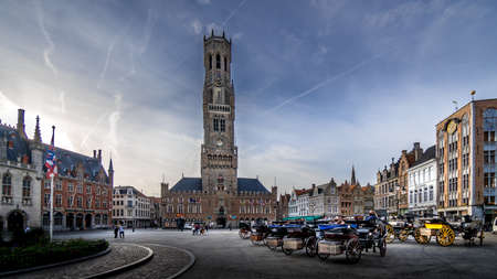 Brugge/Belgium - Sept. 20 2018: Horse Drawn Carriages at Sunrise on the Market Square in Bruges with many Historic Buildings and famous Belfry Tower built in 1240 and restored from a fire in 1280