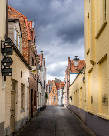 Bruges/Belgium-Sept 19, 2018: Typical cobblestone street with brick houses with step gables in the historic city of Bruges, Belgium