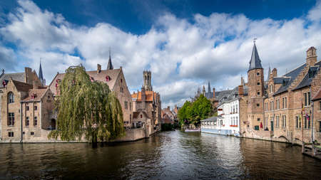 View of the historic buildings and the Belfort Tower from the Dijver canal in the medieval city of Bruges, Belgium