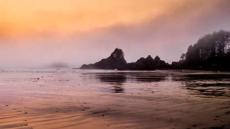 Sunset causing an Orange Glow over the Fog hanging over the rocky shore between Cox Bay and Chesterman Beach at the Pacific Rim National Park on Vancouver Island, British Columbia Фото со стока