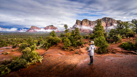 Woman looking at the Red Rocks of Munds Mountain and Surrounding Mountains near the town of Sedona in northern Arizona in Coconino National Forest, USA