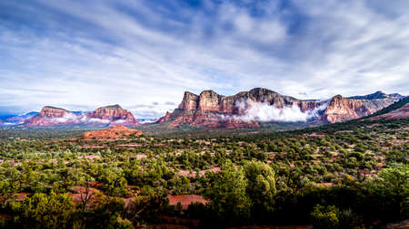 Low Cloud hanging around the Red Rocks of Munds Mountain and Twin Buttes after a heavy rainfall near the town of Sedona in northern Arizona in Coconino National Forest, USA