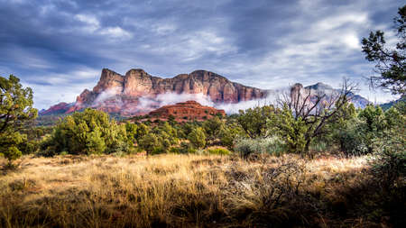 Low Cloud hanging around the Red Rocks of Munds Mountain after a heavy rainfall near the town of Sedona in northern Arizona in Coconino National Forest, USA Фото со стока
