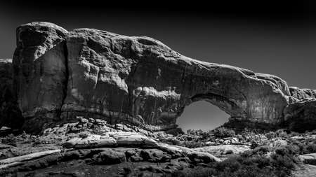 Black and White Photo of the North Window Arch, one of the many large Sandstone Arches in Arches National Park, Utah, United States Фото со стока