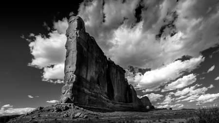 Black and White Photo of tall and fragile sandstone Rock Fin names the Tower of Babel in the desert landscape of Arches National Park, Moab, Utah, USA