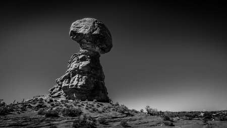 Black and White Photo of Balanced Rock, a tall and delicate sandstone Rock Formation in the desert landscape of Arches National Park, Moab,  Utah, USA