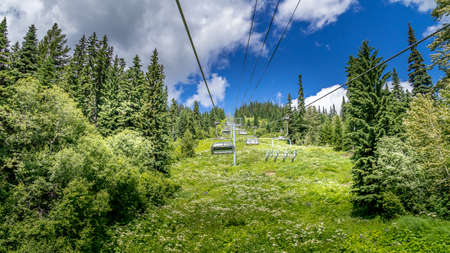 Riding the Chairlift up for a hike on Tod Mountain at Sun Peaks village in the Shuswap Highlands of British Columbia, Canada Фото со стока