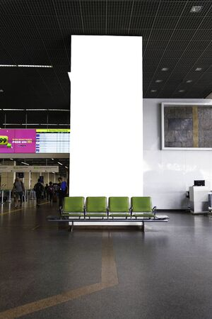 Airport seats with a blank wall for advertising.