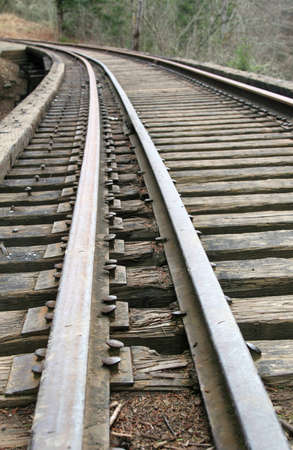 wood railroads: Railroad tracks about to curve in the mountains.