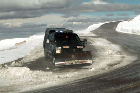 snow plow: A snow plow clearing the road on top of a mountain in Colorado.