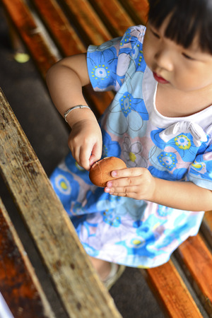 A little girl peeling off egg shell of a hard boiled egg
