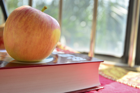 cornerstone: Close up to an apple on a book