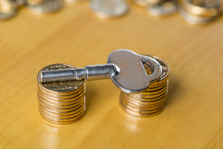 bonanza: Gold money coins with an antique key Stock Photo