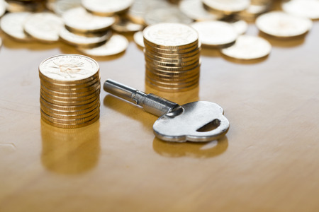 antique coins: Gold money coins with an antique key Stock Photo