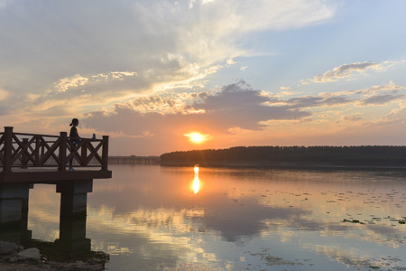 soul searching: At sunset, woman  exercise on the wooden bench