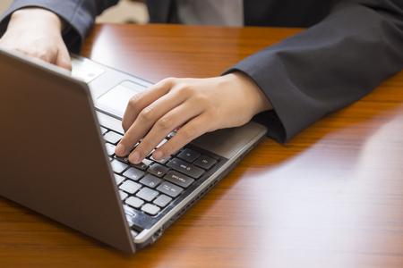 operating key: Woman working on laptop Stock Photo