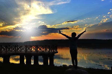 soul searching: Woman standing beside lake with sunset scenery Stock Photo