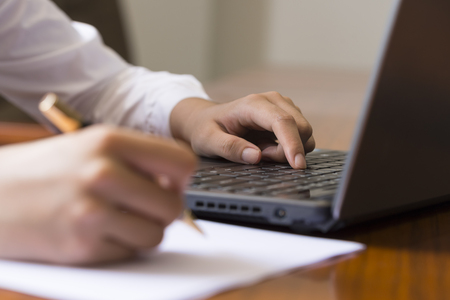 press agent: Young woman with a pen in front of the laptop to work