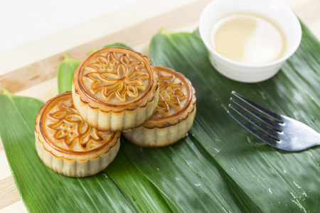 tileable: Stack of moon cakes, tea, fork on the background of bamboo leaves