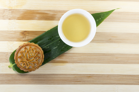 A mooncake, tea on the background of bamboo leaves