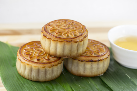 consciously: Stack of moon cakes, tea on the background of bamboo leaves Stock Photo