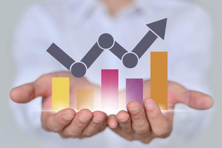 A businessman holding financial growth chart