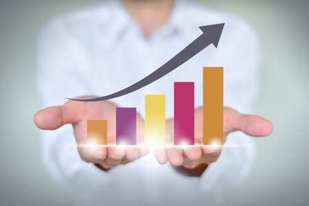 A businessman holding economic growth chart