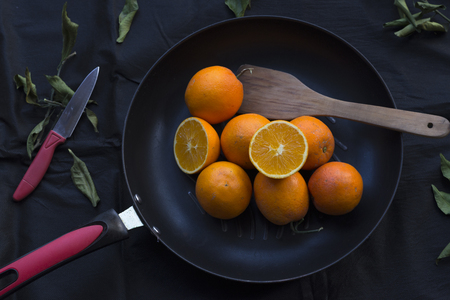 dode bladeren: Oranges in the pan, black linen background, strewn with dead leaves