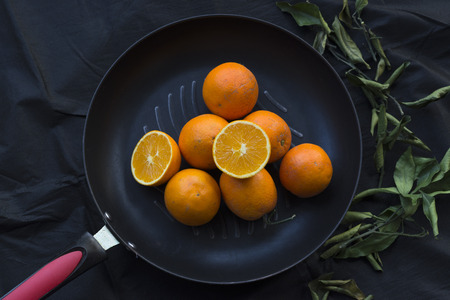 Close up to oranges in a pan on black background Stock Photo