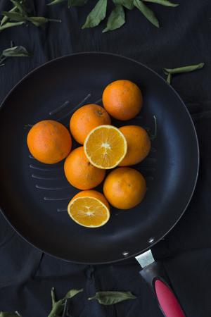 Cierre de naranjas en una sartén sobre fondo negro