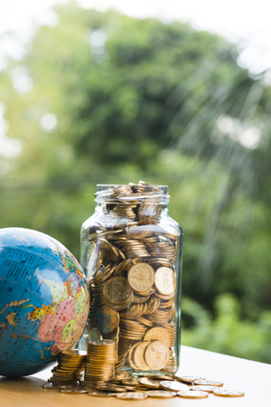 A jar of coins full of coins; a deposit of gold coins; a globe