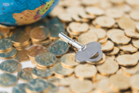 Stacked gold coins, keys and globes Stock Photo