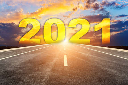 The 2021 numbers at sunrise are written on the road straight ahead 版權商用圖片