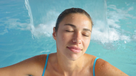 Beautiful young girl (woman) relaxed in a hydromassage bath, in a blue bathing suit, on a blue background. Concept: spa procedures, body massages, spa cream, relaxation, spa water treatments, swimming pool